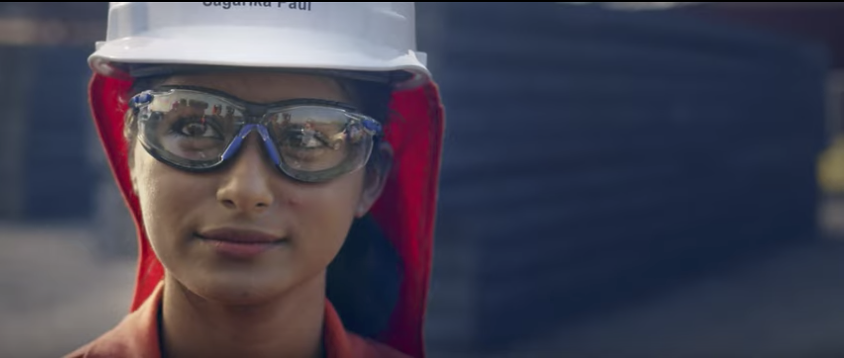 A woman wearing a construction hat and goggles
