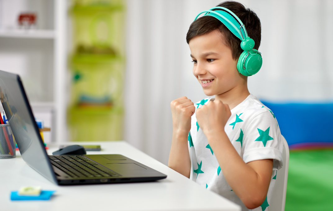 Child using laptop with headphones, excited