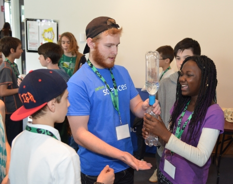 Let's Talk Science Outreach volunteer works with students to do a hands-on science activity